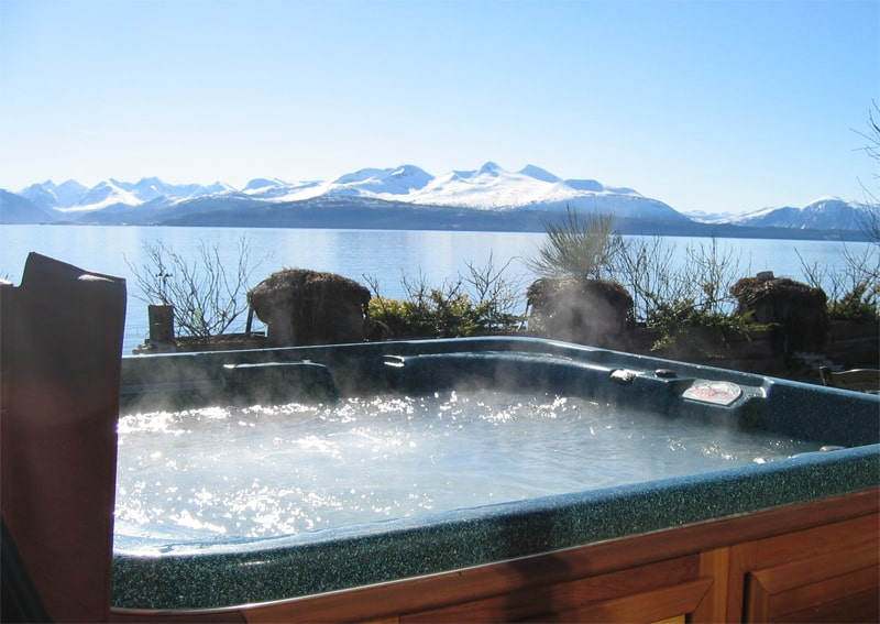 arctic spas hot tub with a view of lake and mountains covered with snow view