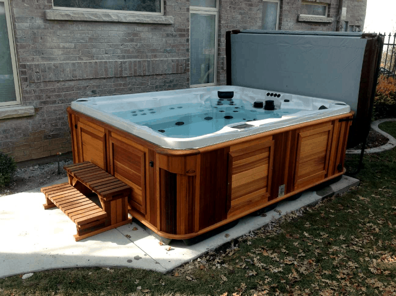 Arctic Spas Hot tub with an open cover in the backyard